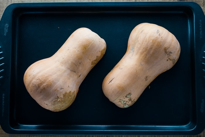 Butternut squash halves face down on a baking tray.