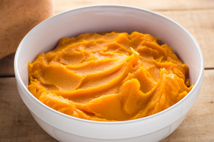 Homemade butternut squash puree in a white serving bowl.