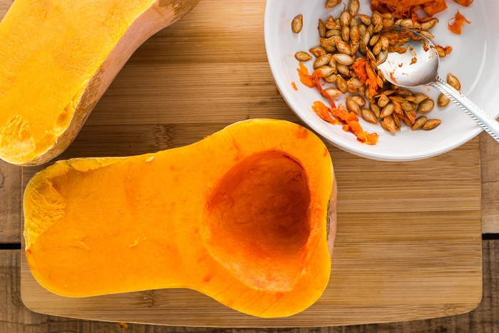 Butternut squash with seeds and pulp removed on a cutting board.