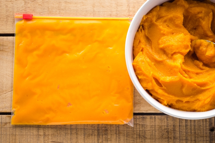 Freezer bag with puree laying flat next to a bowl of butternut squash puree.