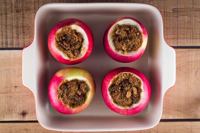 4 apples in a baking dish filled with sugar, cinnamon, and raisins.