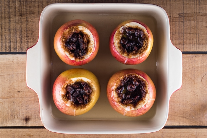 4 baked apples in a red and white baking dish ready to serve.