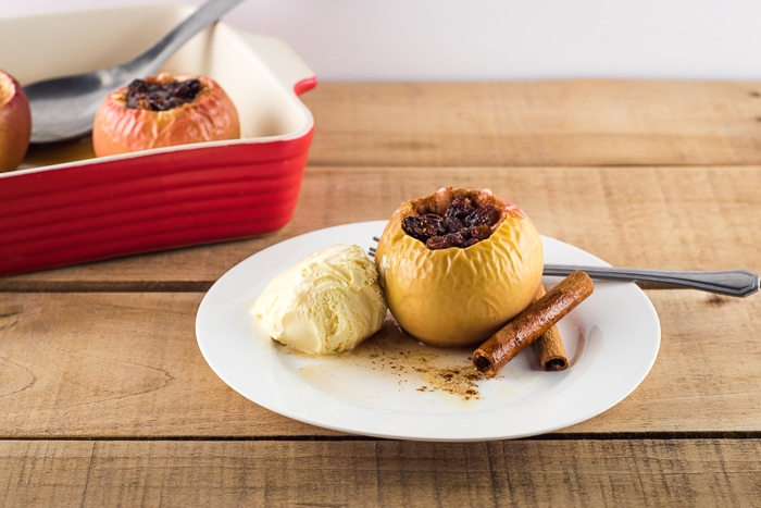 Baked apple served with vanilla ice cream on a white plate.