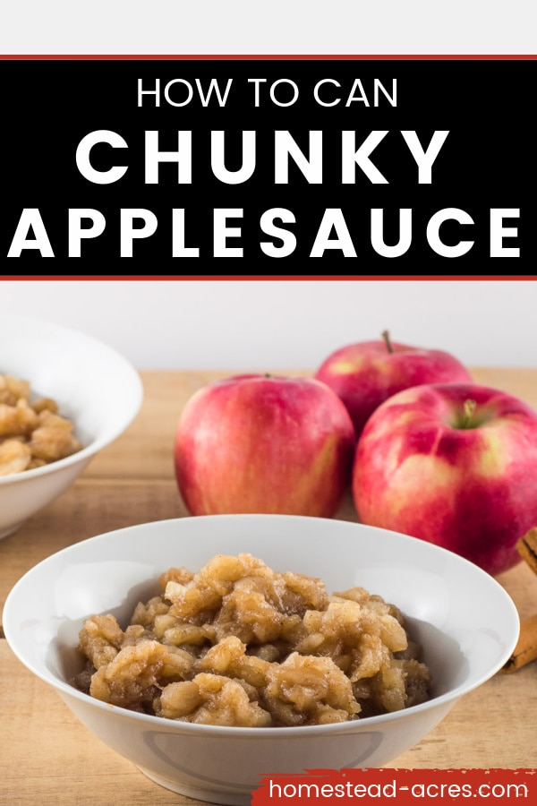 White bowl of chunky applesauce on a wooden table with another bowl of applesauce in the background along with 3 red apples. Overlay text reads How To Can Chunky Applesauce.