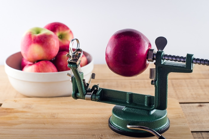 Crank apple peeler and corer with a red apple on it ready to be peeled.