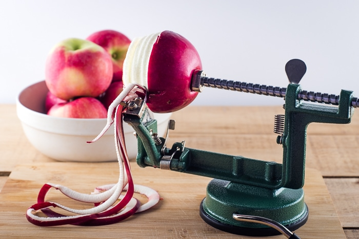 Peeling apples for applesauce with a hand crank peeler.
