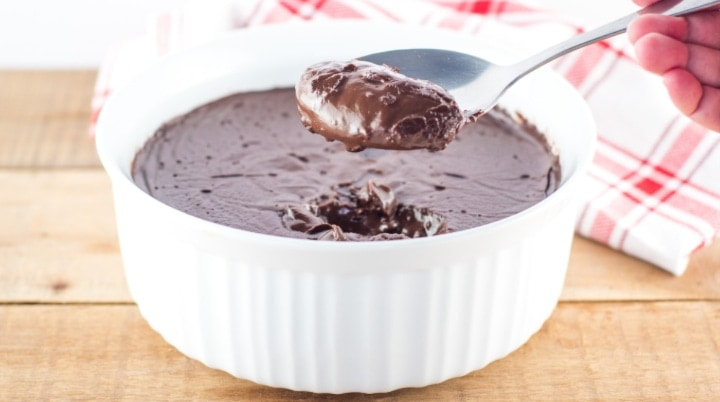 Homemade chocolate pudding in a white bowl on a wooden table. There is a large spoonful of pudding being held over the bowl and a red and white tea towel in the background.