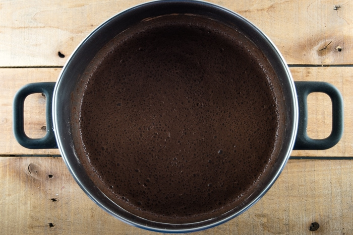 Milk mixed into the dry ingredients for homemade chocolate pudding in a lrage pot on a wooden background.