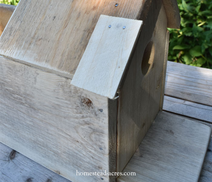 Adding shingles to a birdhouse planter roof.
