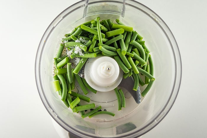 Garlic scapes, salt and pepper in a food processor bowl.