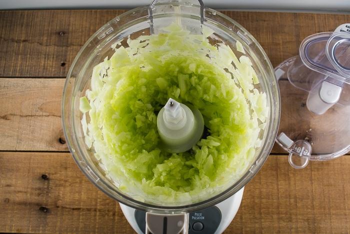 Chopped cucumbers in a food processor.