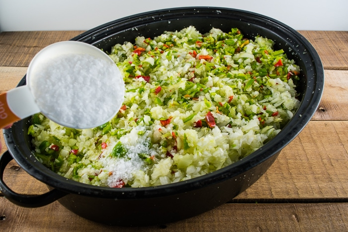 Adding salt to the vegetable mixture in a roasting pan.