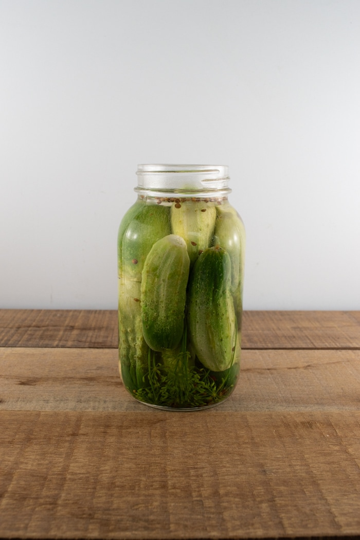 Jar filled with brine, spices, and cucumbers for homemade whole dill pickles.