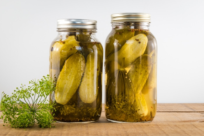 2 quart jars of homemade dill pickles sitting on a wooden table with fresh dill next to them.