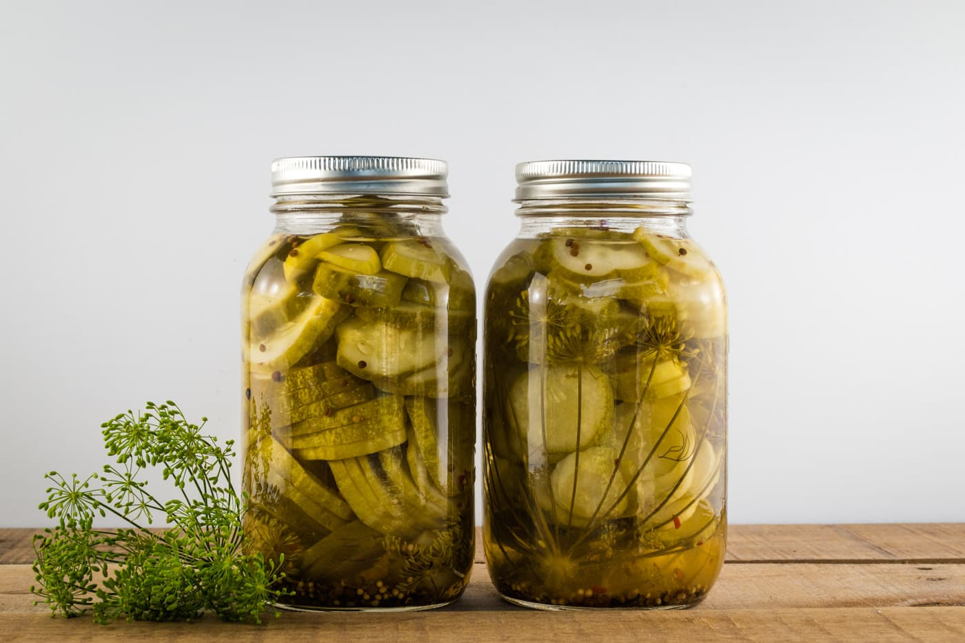 Sliced round dill pickles perfect for hamburgers in large canning jars with fresh dill next to them.
