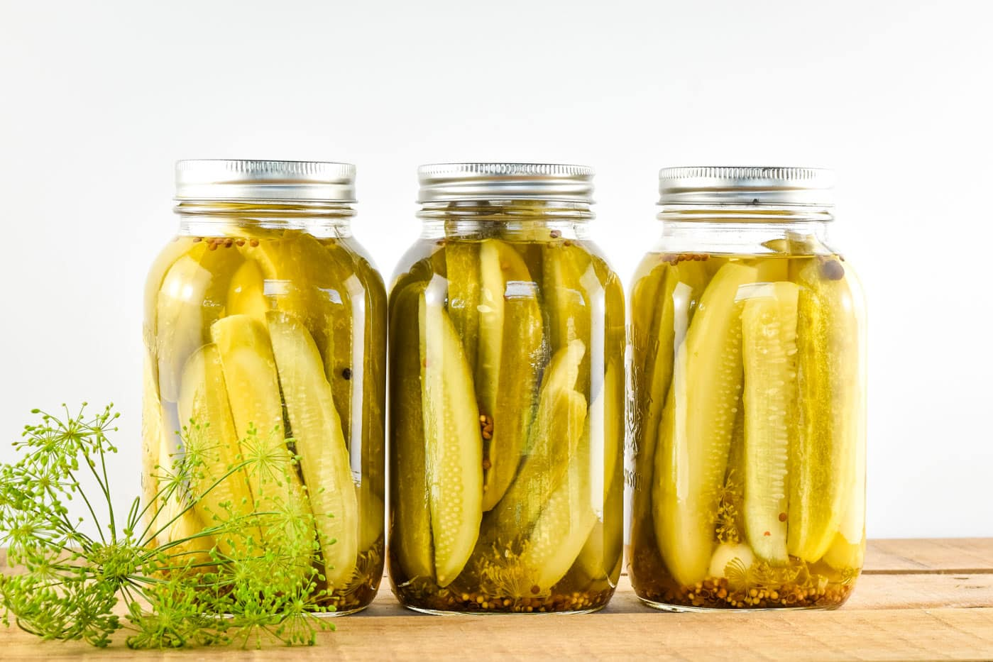 Homemade dill pickle spears in quart mason jars on a wooden table with fresh dill next to the jars.