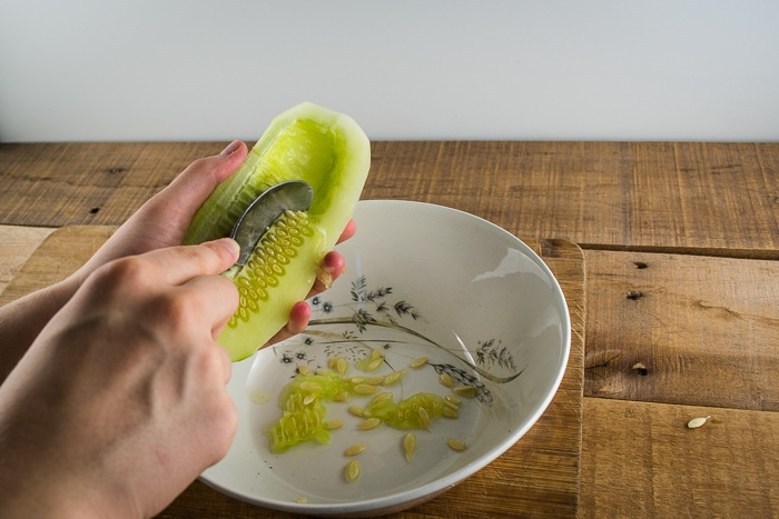Scooping out cucumber seeds with a spoon.