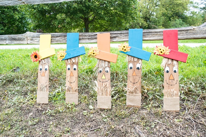 Set of 5 super cute wooden scarecrow faces decorated for fall and set along a fence.