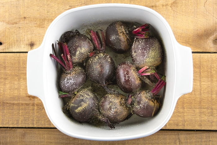 Beets in a greeced white baking dish and sprinkled with salt and pepper/