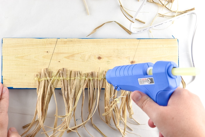 Adding layer of hot glue over the raffia to secure it.
