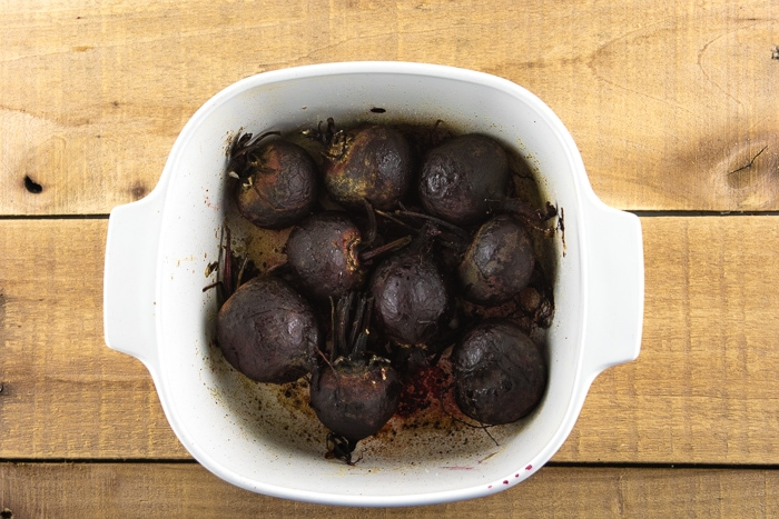 Fully cooked roasted beets in a white baking dish on a wooden table.