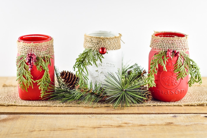 Christmas painted mason jar centerpiece with burlap, greenery and berries.