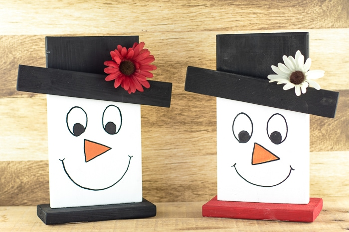 Cute little smiling snowman faces on a side table. One has a hat decorated with a red flower, the other a white flower.