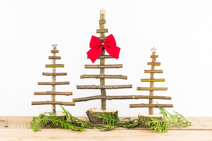 Set of 3 small twig trees for centerpieces decorated with a red bow and stars with greenery around the base.