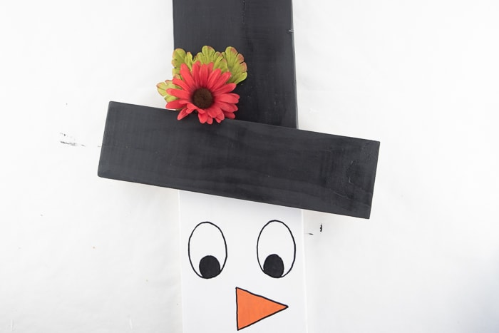 Snowman hat with flowers and leaves glued on.
