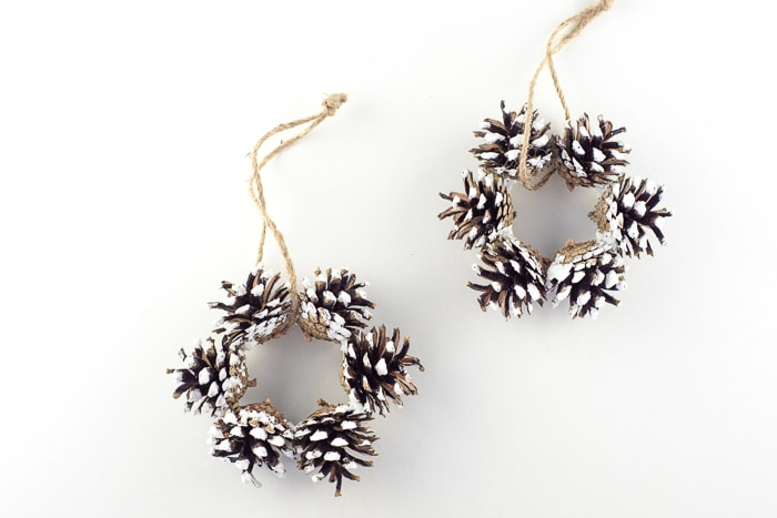 2 mini pinecone wreaths with the tips painted white and added sparkles. Each have a twine hanging tied around them.