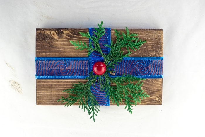 Wooden present decorated with ribbon, greenery and a berry.