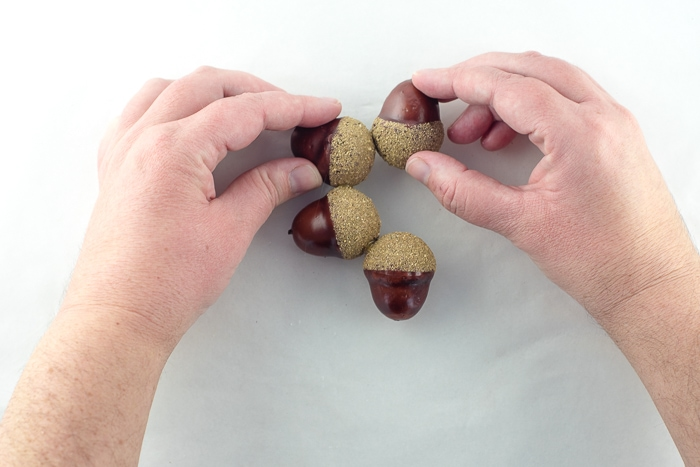 Half of the acorn wreath glued into a circle. Holding the next two acorns steady until the glue sets.