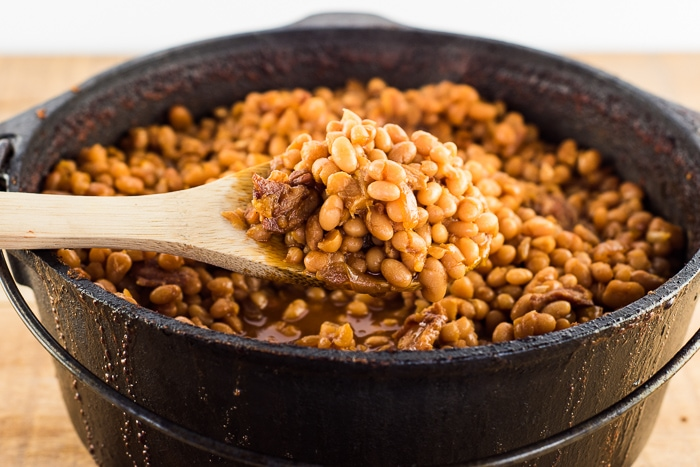 Full pot of baked beans in a dutch oven. With a spoon full being held up on a wooden spoon.