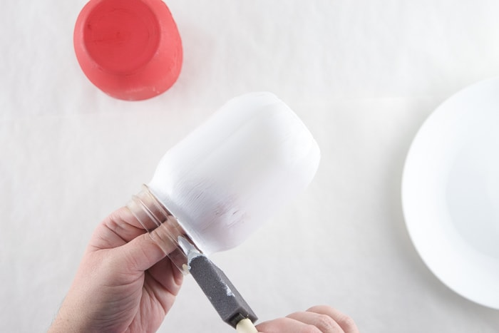 Painting a mason jars white chalk paint.