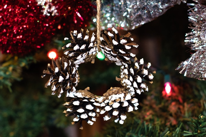 Rustic snowy pinecone wreath ornament hanging on a Christmas tree.