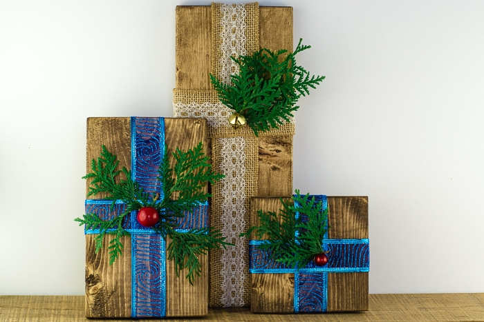 Set of 3 homemade wooden presents decorated with blue ribbon, burlap ribbon, greenery, berries, and bells.