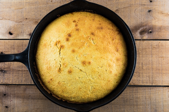 Warm homemade skillet cornbread in a cast iron skillet on a wooden table.