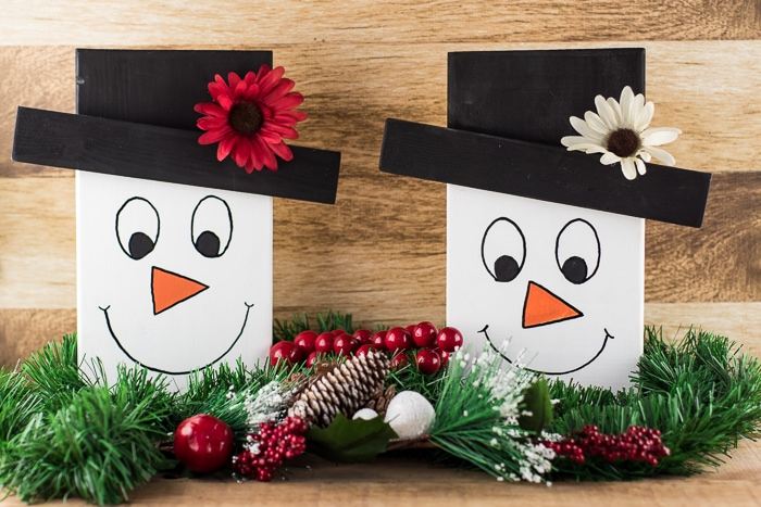Cute tabletop snowman faces made out of wood on a side table with greenery, berries, and pinecones tucked around them.