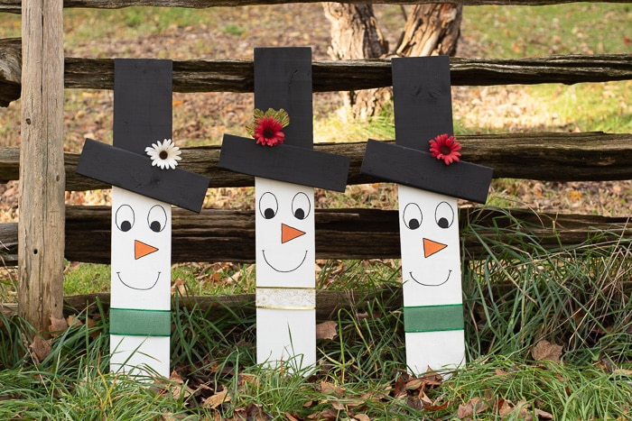 3 Cute wooden snowman faces leaning against a fence.