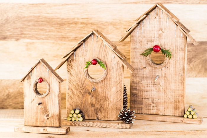 3 sizes of handmade birdhouse Christmas ornaments. Decorating with nautical rope around the openings with greenery and berries.