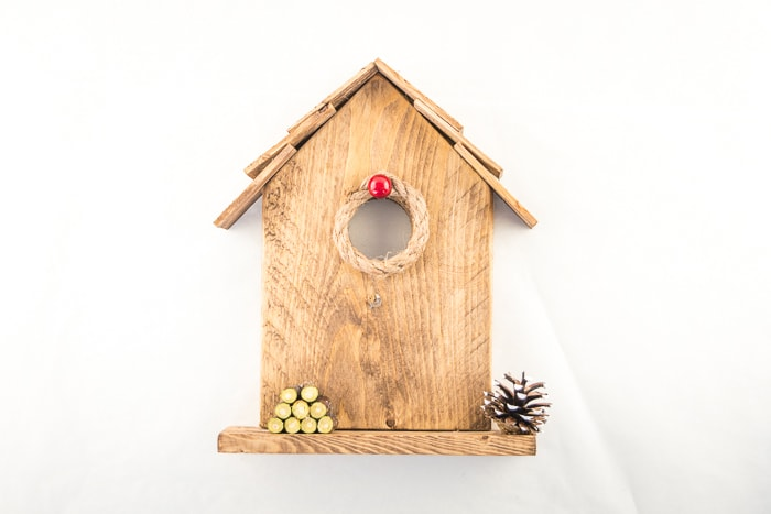 Completed birdhouse tabletop ornament with nautical rope and a berry around the opening, a painted pinecone and logs decorating the base.