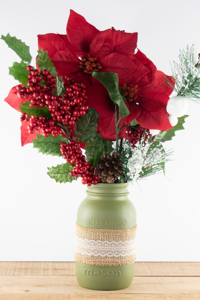 Painted green mason jar with burlap ribbon around the center holding Christmas greenery and poinsettia flowers and berries.