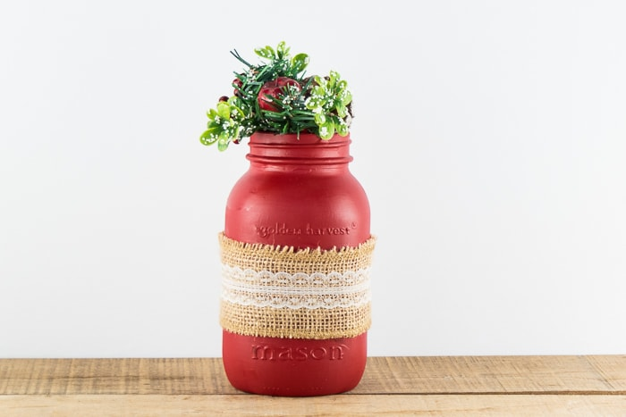 Red mason jar holding Christmas greenery.
