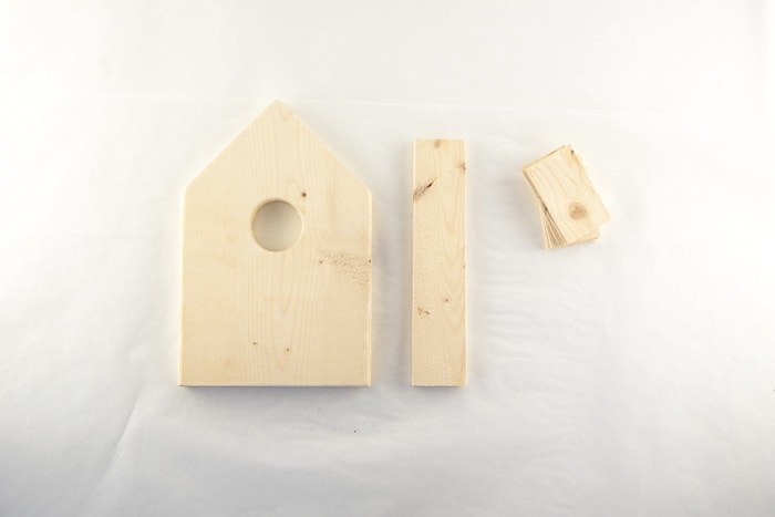 Wood cut outs for the birdhouse ornament base, face, and roof.