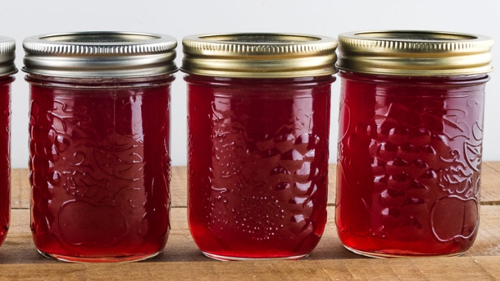 3 jars of red jelly sitting on a wooden table top