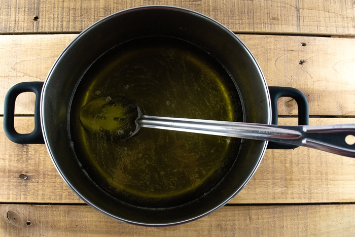 Dandelion syrup in a large pot on a wooden table.