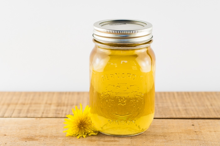 Dandelion simple syrup in a mason jar on a wooden table with a dandelion flower next to the jar.