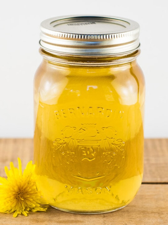 Dandelion syrup in a pint mason jar sitting on a wooden table with a dandelion flower next to it.
