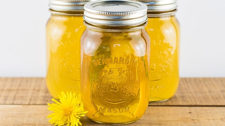 3 jars of dandelion syrup set on a wooden table with a dandelion flower next to them.