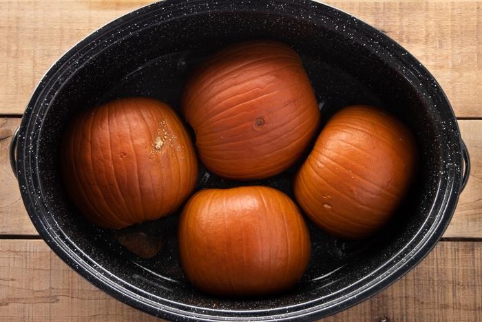Roasted pie pumpkins in a roasting pan.